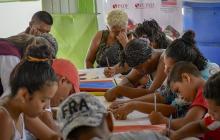 Un grupo de venezolanos participa de una actividad psicosocial en el comedor del hogar de paso.