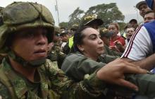 Agentes de la policía colombiana escoltan a un miembro femenino de las Fuerzas Armadas Nacionales Bolivarianas de Venezuela (FANB), que desertó, cerca del puente internacional Simón Bolívar en Cúcuta.