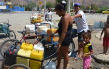Familia traslada bidones de agua en carretillas.