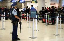 Un policía vigila el arribo de pasajeros al aeropuerto de Christchurch, Nueva Zelanda, epicentro de un ataque  armado mortal.