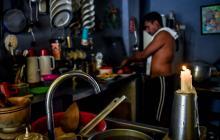 Guillermo Cortezano prepara el almuerzo en la cocina de su casa con una vela encendida, ya que no había fluido eléctrico en el momento.
