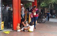 Una mujer busca unas  monedas para dárselas a una adulta con dos niños.