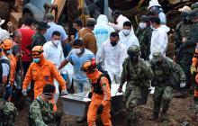 Voluntarios, miembros de Defensa Civil y soldados trasladan dos cuerpos.