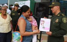 El general Mariano Botero Coy entrega un impreso a una mujer.