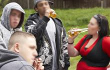 Varios jóvenes están reunidos consumiendo bebidas alcohólicas y sustancias psicoactivas en un parque.