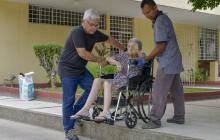 Dos hombres ayudan a bajar a una mujer en silla de ruedas, en un bordillo alto y con solo escaleras al ingreso.