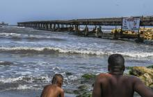 Un hombre junto con su hijo observan  parte de la estructura vieja del muelle de Puerto Colombia.