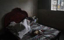 Un indígena Yukpa con malaria permanece envuelto en las sábanas junto a su bebé.