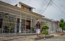 Una mujer barre la puerta en una casa enrejada de techo a piso en un sector del barrio Universal, en la localidad Suroriente.
