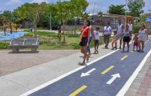 Wendy Carrillo, futura reina de las fiestas del barrio, camina junto a su familia y vecinos por un parque.