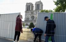 Los trabajadores instalan barreras frente a la catedral de Notre-Dame en París antes de un trabajo de descontaminación.