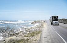 Una mula cruza por la vía Barranquilla- Ciénaga, donde se ve el mar a pocos metros de la vía.