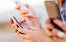 Personas con sus teléfonos celulares.
