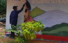 Un excombatiente borrando el mural de 'Santrich'.