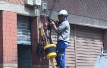 Un trabajador del sector eléctrico realiza reparaciones en las instalaciones de un local comercial.