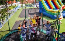 Una decena de niños del barrio La Manga salta en una de las atracciones del parque de la cra 15 con 84.