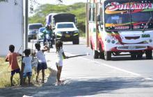 Con una rama que parece una caña para pescar, los niños piden dinero a quienes transitan por la vía .