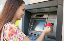 Una persona saca dinero en un cajero electrónico de una entidad bancaria.