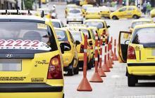 Varios taxis transitan por una calle de Barranquilla.