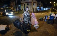 Una mujer de nacionalidad venezolana camina con colchones en la mano buscando un lugar para dormir.