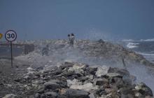 Turistas intentan tomarse una foto y el mar alcanza a salpicarlos.