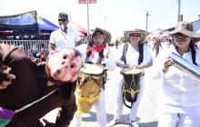 Uno de los integrantes de la danza imita los movimientos de un primate, acompañado de un grupo de millo durante la Batalla de Flores.