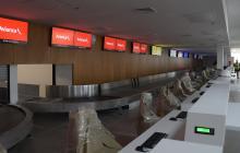 Área de 'check in' con sus pantalllas y sistema de registro de maletas de viajeros.
