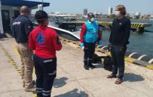 Personal de autoridad marítima de Cartagena atiende a uno de los extranjeros que llegó a bordo de uno de los tres veleros.