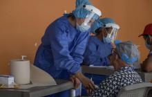 Personal médico usando protección examina a pacientes de la tercera edad.
