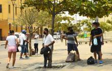 Un grupo de personas caminan por la esquina de la iglesia de San Roque, en el centro de la ciudad. Tres