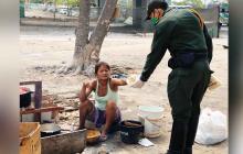 Policía entrega una porción de pan a una mujer.