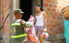 Una habitante de Atánquez recibe ayuda humanitaria de manos de un soldado.
