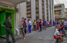 Subsidiados en el centro de Barranquilla a la espera de cobrar  su pago en un cajero electrónico.