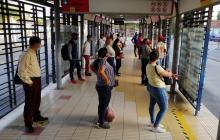 Varios usuarios esperan la ruta en una estación.