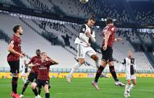 Cristiano Ronaldo salta en busca del balón ante la marca de defensores del Milan