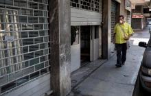 Fotografía de un hombre con tapabocas caminando frente a un local comercial entreabierto en Caracas (Venezuela).