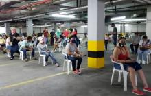 Clientes permanecen sentados guardando la distancia en el parqueadero de un centro comercial de Cartagena.