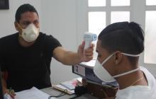 Maikol Ortiz, kinesiólogo de Junior, le mide la temperatura a Gabriel Fuentes durante los exámenes médicos generales a los que se sometieron los jugadores el sábado.