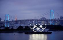Los aros olímpicos iluminan el agua cerca del Puente del Arco Iris en el Parque Marino de Odaiba (Japón).