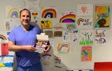 """Pons al lado del """"muro de la esperanza"""" que ha habilitado en el hospital en el que trabaja en Inglaterra."""