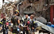 La defensa civil francesa se para alrededor de un área dañada en Beirut.
