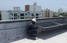 Un operario de Ingelnet instala un panel solar sobre el techo de una vivienda en el norte de Barranquilla.