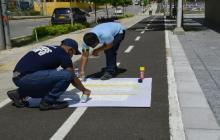 Dos hombres pintan la ciclorruta de la Plaza de La Paz.
