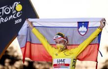Pogacar muestra orgulloso la bandera de Eslovgenia durante la premiación del Tour de Francia.