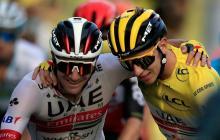Tadej Pogacar, de amarillo, se abraza con un compañero durante la última etapa del Tour de Francia.