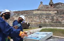 Dos empleados de la Escuela Taller Cartagena permanecen a la entrada del Castillo San Felipe.