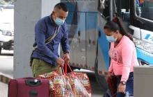 Usuarios de la terminal de transporte terrestre se protegen con tapabocas como medida de prevención contra el coronavirus, en Bogotá.