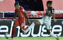 Gabriel Fuentes tratando de detener la proyección ofensiva de Cristian Arrieta.