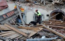 Un trabajador de rescate busca entre los restos de un edificio derrumbado.