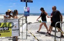 Varias personas pasean por la playa en Guarujá, San Pablo, sin usar el tapabocas.